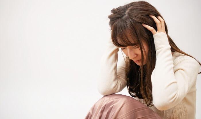 頭を抱えて泣く女性